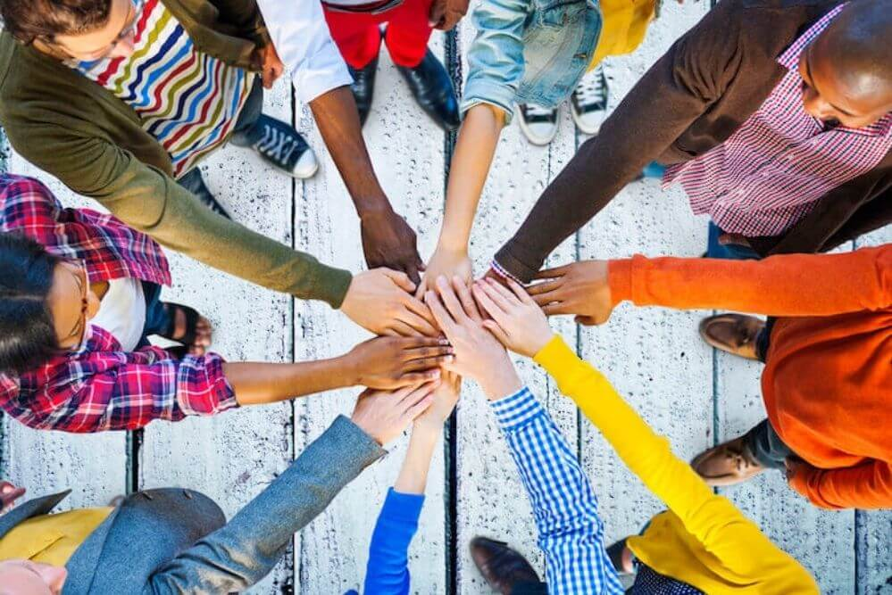 View from above of people standing in a circle and celebrating community by placing their hands over each others in the middle